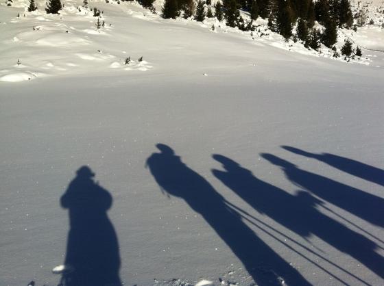 gruppo di ciaspolatori in sosta sotto il sole